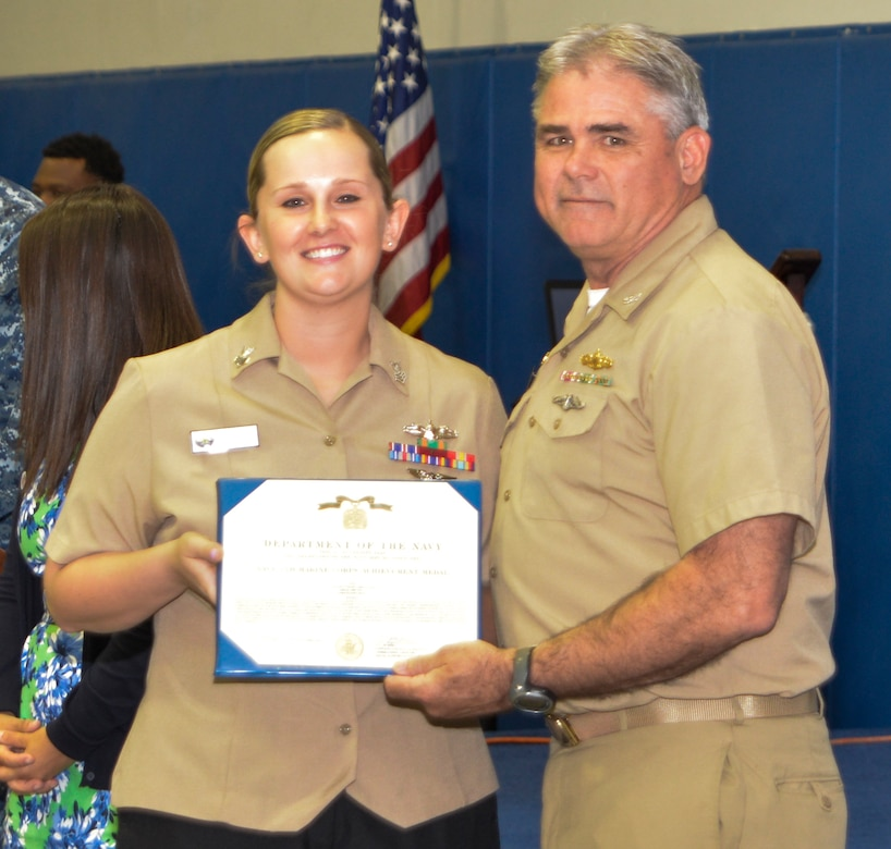 Captain Timothy Sparks, Joint Base Charleston deputy commander, presents the Navy Achievement Medal to MM1 Ashley Pruitt, Nuclear Power Training Unit, during the Sexual Assault Prevention and Response Program luncheon April 30, 2015 at Joint Base Charleston – Weapons Station, S.C. The Navy Achievement Medal was presented to Pruitt for her dedicated to the SAPR program through volunteer hours, donations raised, victim response and education and awareness.  (U.S. Air Force photo/Seamus O'Boyle)
