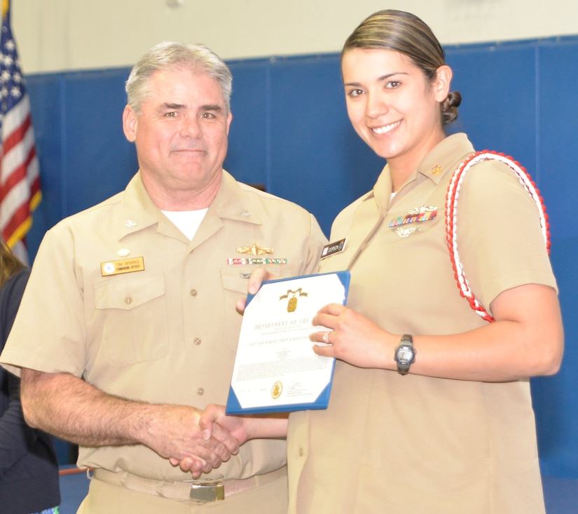 Captain Timothy Sparks, Joint Base Charleston deputy commander, presents the Navy Achievement Medal to MMC Erica Dopson, Naval Nuclear Power Training Command, during the Sexual Assault Prevention and Response Program luncheon April 30, 2015 at Joint Base Charleston – Weapons Station, S.C. The Navy Achievement Medals were presented to Dopson for her dedicated to the SAPR program through volunteer hours, donations raised, victim response and education and awareness. (U.S. Air Force photo/Seamus O'Boyle)