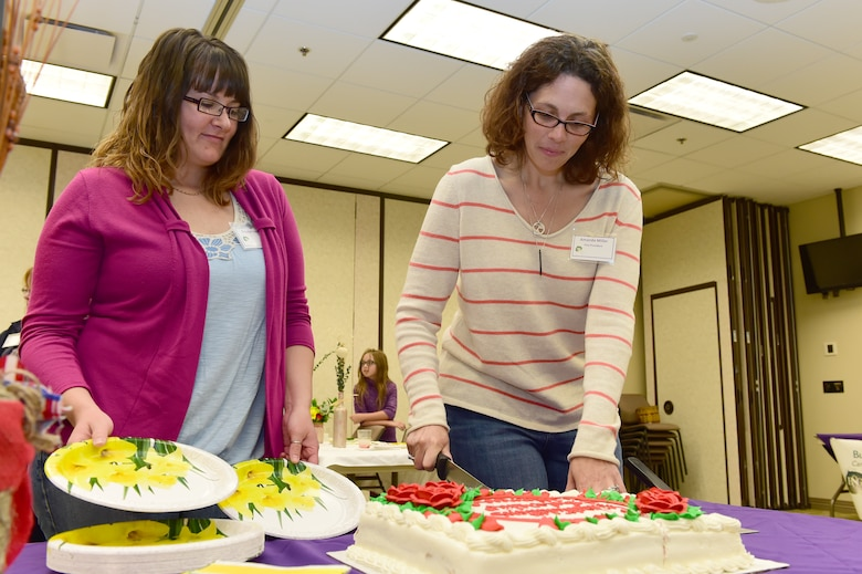 Amanda Miller, Buckley Spouses' Group Vice President, cuts a cake celebrating the scholarship winners May 9, 2015, on Buckley Air Force Base, Colo. The Spouses' Group raised and gave away $5,000 in scholarship funds to show support for individuals who are looking to advance through higher education. (U.S. Air Force photo by Airman 1st Class Luke W. Nowakowski/Released)