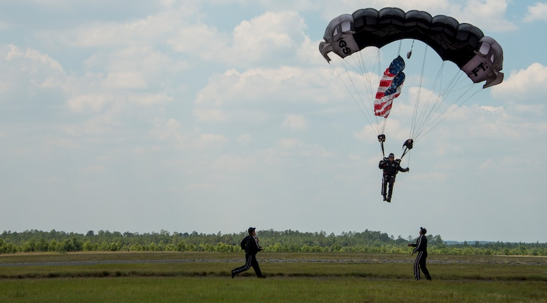 Members of the parachute team help a soldier as he lands during a demonstration at the Rangers' Open House event May 9 at Eglin Air Force Base, Fla. The event was a chance for the public to learn how Rangers train and operate. The event displays showed equipment, weapons, a reptile zoo, face painting and weapon firing among others. The demonstrations showed off hand-to-hand combat, a parachute jump, snake show, and Rangers in action. (U.S. Air Force photo/Tech. Sgt. Jasmin Taylor)