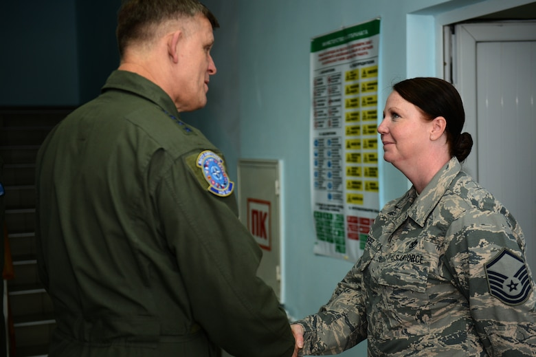 U.S. Air Force Master Sgt. Christina Lopez, 52nd Civil Engineer Squadron requirements and optimization section chief, receives a coin from U.S. Air Force Gen Frank Gorenc, U.S. Air Forces in Europe and Air Forces Africa commander, during a visit to Graf Ignatievo Air Base, Bulgaria, May 11, 2015. Gorenc recognized Lopez for her contributions in establishing the initial footprint of Theater Security Package support personnel. (U.S. Air Force photo by Senior Airman Gustavo Castillo/Released)