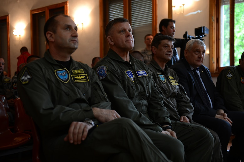 Maj. Gen. Rumen Radev, Bulgarian Air Force commander, left, U.S. Air Force Gen. Frank Gorenc, U.S. Air Forces in Europe and Air Forces Africa commander, center, and Lt. Gen. Constantin Popov, Bulgarian deputy chief of defense, wait to take the stage during a briefing to U.S. and Bulgarian Airmen about the Theater Security Package deployment during a visit to Graf Ignatievo Air Base, Bulgaria, May 11, 2015. The briefing, attended by local media, showcased partnered U.S. and Bulgarian commitment to the current and future security and stability of the region. (U.S. Air Force photo by Senior Airman Gustavo Castillo/Released)