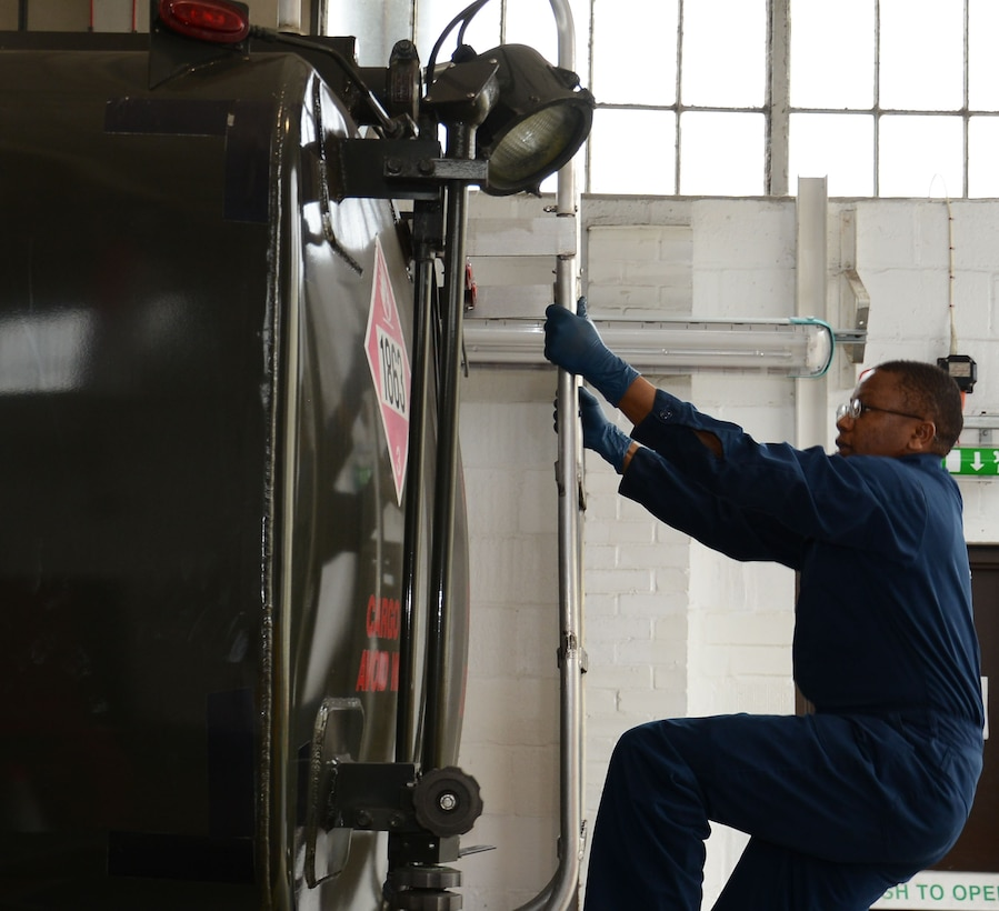 U.S. Air Force Staff Sgt. Peter Mwangi, 100th Logistics Readiness Squadron NCO in charge of refueling maintenance from Las Vegas, Nev., climbs to the top of a fuel truck to perform maintenance April 23, 2015, on RAF Mildenhall, England. Mwangi climbed the truck to work on the refueling hose. (U.S. Air Force photo by Gina Randall/Released)