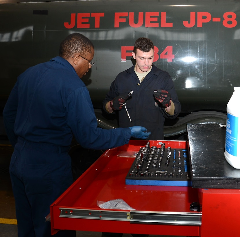U.S. Air Force Staff Sgt. Peter Mwangi, left, 100th Logistics Readiness Squadron NCO in charge of refueling maintenance from Las Vegas, Nev., and U.S. Air Force Airman 1st Class Jacob Rievel, 100th LRS Refueling Maintenance journeyman from Johnstown, Pa., discuss what tools they will need for maintenance April 23, 2015, on RAF Mildenhall, England. Mwangi and Rievel prepared for maintenance on an R-11 fuels truck that delivers fuel to aircraft and fuels storage facilities on base. (U.S. Air Force photo by Gina Randall/Released)