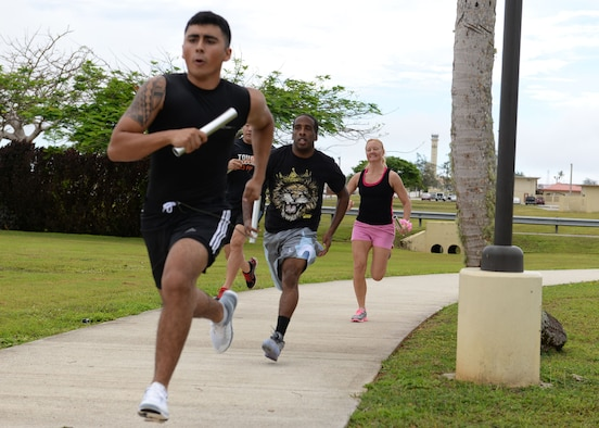 Racers sprint during a baton relay race May 8, 2015, at Arc Light Park, Andersen Air Force Base, Guam. The race was part of the Gladiator Glide, a base-wide morale event held by the Coral Reef Fitness Center, that consisted of several competitions including a baton relay, sack race, wheelbarrow race and a pie eating contest. (U.S. Air Force photo by Airman 1st Class Joshua Smoot/Released)