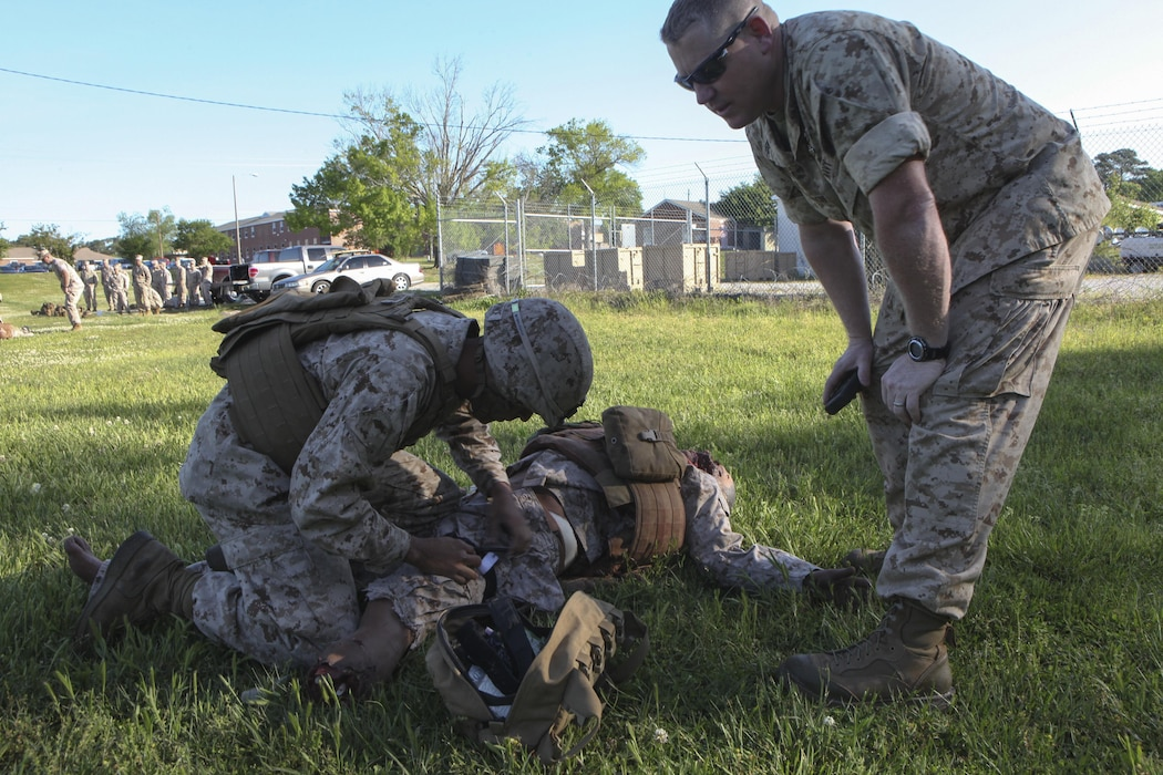 Pfc. Kevin J. Oronaponce, a rifleman with 2nd Battalion, 2nd Marine Regiment, applies a tourniquet to a mannequin during the final test for the Combat Trauma Care Course aboard Camp Lejeune, N.C., April 24, 2015. The mannequins were equipped with a system that allows artificial blood to bleed from various wounds and recorded voices to talk, providing a more realistic experience. (U.S. Marine Corps photo by Pfc. David N. Hersey/Released)