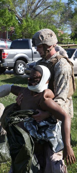Lance Cpl. Kyle Ward, a mortarman with 2nd Battalion, 2nd Marine Regiment, 2nd Marine Division, drags a simulated casualty to an evacuation site during the final exam for the Combat Trauma Care Course with the Division Combat Skills Center aboard Camp Lejeune, N.C., April 24, 2015. During the test, the Marines were required to run the length of a softball field and reach one of three mannequins. Under the watch of the instructors, the Marines treated the individual wounds on each of the bodies before calling in for evacuation and preparing them for transport. (U.S. Marine Corps photo by Pfc. David N. Hersey/Released)