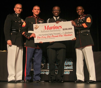 Captain Kevin M. Lowe, executive officer for Recruiting Station Orlando, Sgt. Garrett R. Rice, canvassing recruiter for Recruiting Substation Melbourne and Gunnery Sgt. Davon G. Butler, station commander for RSS Melbourne, present Nathaniel Barthelemy, a senior from Bayside High School, with the NROTC Check at Bayside High School May 11, 2015. Recipients have the opportunity to become Marine officers upon completion of their degree after high school.