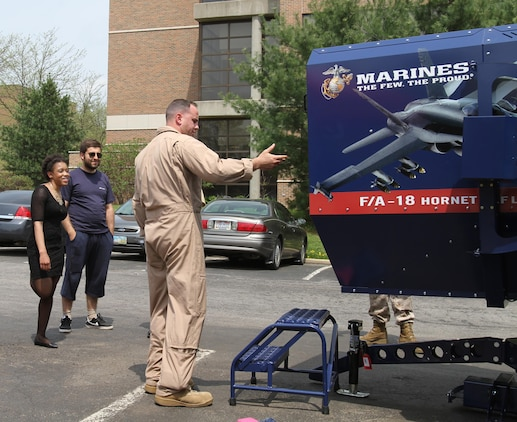 U.S. Marine Corps Capt. Richard O'brien an F/A-18 weapons systems officer and the aviation assistant procurement for the eastern recruiting region, Parris Island, South Carolina, shows students from Kent State University the 4th Marine Corps District F/A-18 full-motion flight simulator May 5, 2015.  The Marines bring the simulators to college campuses to build awareness and enthusiasm among students and campus faculty regarding Marine officer programs. (U.S. Marine Corps photo by Cpl. Kyle Welshans/Released)