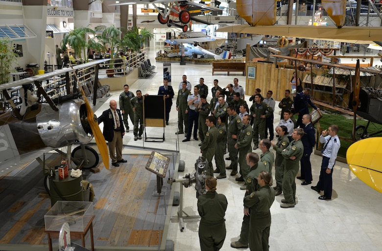 Tim Reuters, former Army helicopter pilot and National Naval Aviation Museum volunteer, guides  451st Flying Training Squadron students  through the museum's World War I exhibit on Naval Air Station Pensacola May 8, 2015. The students learned about naval aviation history as a part of the Doolittle Raiders celebration. (U.S. Air Force photo/1st Lt. Ben Sowers)