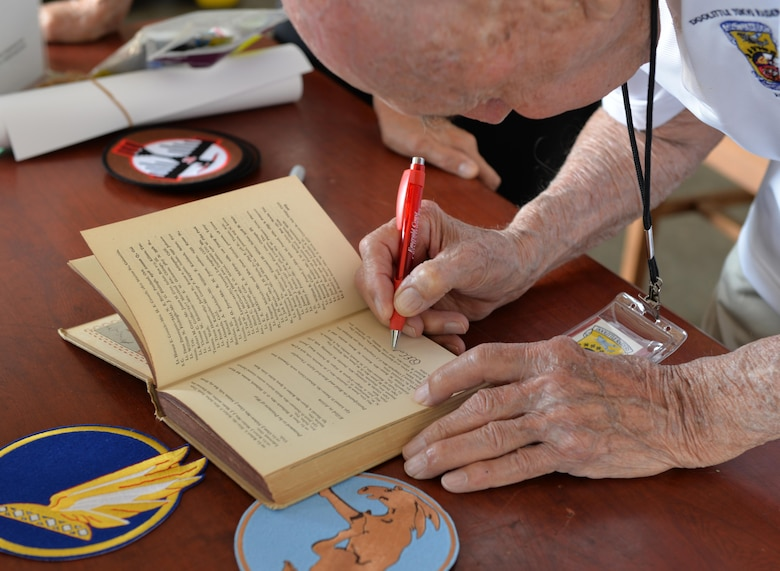 Retired Lt. Col.  Dick Cole signs a book at the Doolittle Raiders ceremony at Naval Air Station Pensacola May 8, 2015. Cole was honored at the ceremony, which commemorated the 80 men who flew B-25 Mitchell bombers over Tokyo after the Japanese attacked  Pearl Harbor. (U.S. Air Force photo/1st Lt. Ben Sowers)