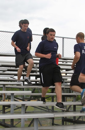 Dylan DeYoung, center, a poolee with Permanent Contact Station Smithfield, runs on bleachers during a physical training session at Smithfield-Selma High School in Smithfield, North Carolina, April 29, 2015. DeYoung lost more than 70 pounds over the course of 17 months to join the Marine Corps. (U.S. Marine Corps photo by Sgt. Dwight A. Henderson/Released)