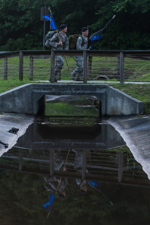 "Airman 1st Class Hunter Dudley and Lt. Col. Warren Brainard, 628th Security Forces Squadron commander, cross a bridge with the squadron guidon and the ""Thin Blue Line"" flag May 12, 2015 at Joint Base Charleston, S.C., during a 24-hour ruck march. The event to honor police officers killed in the line of duty was held as part of the 2015 National Police Week celebration. The 'Thin Blue Line' represents the sacrifices made by those who protect and serve. Events for this year's police week include a picnic, a 24-hour ruck march, a golf tournament, a chili cook-off, motorcycle ride and a retreat ceremony.  (U.S. Air Force photo/Senior Airman Jared Trimarchi)"