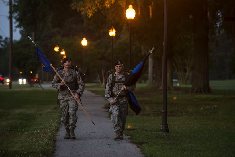 "Airman 1st Class Hunter Dudley and Lt. Col. Warren Brainard, 628th Security Forces Squadron commander, march with the squadron guidon and the ""Thin Blue Line"" flag May 12, 2015 at Joint Base Charleston, S.C., during a 24-hour ruck march.  The event to honor police officers killed in the line of duty was held as part of the 2015 National Police Week celebration. The 'Thin Blue Line' represents the sacrifices made by those who protect and serve. Events for this year's police week include a picnic, a 24-hour ruck march, a golf tournament, a chili cook-off, motorcycle ride and a retreat ceremony.  (U.S. Air Force photo/Senior Airman Jared Trimarchi)"