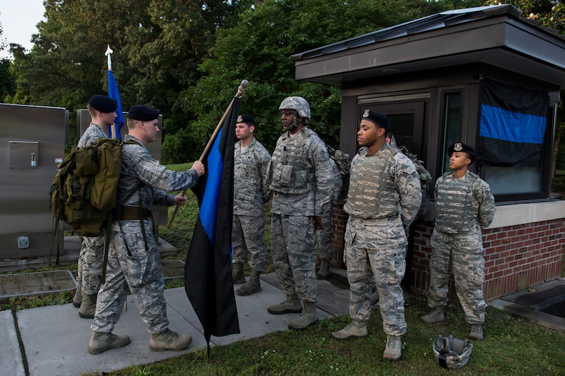 Lt. Col. Warren Brainard, 628th Security Forces Squadron commander, hands off the Thin Blue Line flag to the next group of participants May 12, 2015 at Joint Base Charleston, S.C., during a 24-hour ruck march.  The event to honor police officers killed in the line of duty was held as part of the 2015 National Police Week celebration. The 'Thin Blue Line' represents the sacrifices made by those who protect and serve. Events for this year's police week include a picnic, a 24-hour ruck march, a golf tournament, a chili cook-off, motorcycle ride and a retreat ceremony.  (U.S. Air Force photo/Senior Airman Jared Trimarchi)