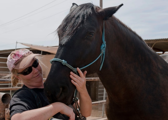 Chanel Jernigan, wife of retired Master Sgt. Stacy Jernigan, pets her horse Zuli at the stables on Nellis Air Force Base, Nev., May 6, 2015. Jernigan brought Zuli back to the United States from Italy. (U.S. Air Force photo by Airman 1st Class Mikaley Towle)