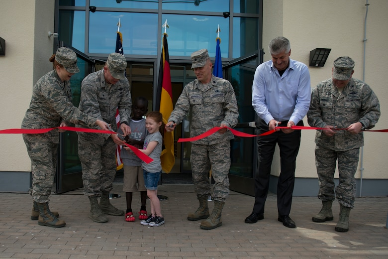 Leadership of the 52nd Fighter Wing and community members perform a ribbon cutting ceremony during the official opening of the new child development center at Spangdahlem Air Base, Germany, May 11, 2015. The new facility can support more than 200 children ages 1-5 and includes a lobby, playground, kitchen and 11 classrooms. (U.S. Air Force photo by Airman 1st Class Luke Kitterman/Released)