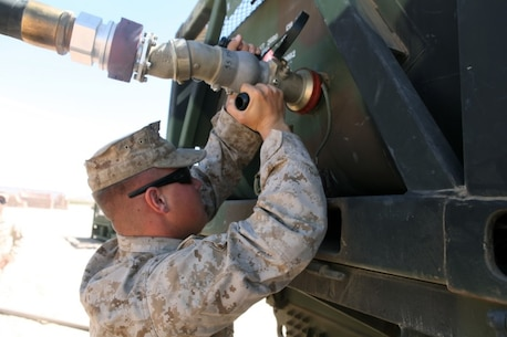 A Motor Transportation Operator with 1st Transport Support Battalion, Combat Logistics Regiment 1, 1st Marine Logistics Group, attaches a fuel hose to an AMK-23 Medium Tactical Vehicle Replacement with the help of two other Marines during routine refueling maintenance on the outskirts of Marine Corps Air Station Yuma, Ariz., April 10, 2015.
