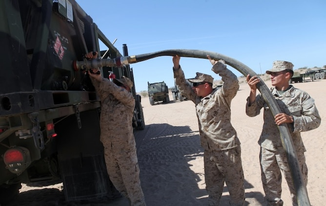 Private First Class Brenen Tischner, left, a Motor Transportation Operator, with 1st Transport Support Battalion, Combat Logistics Regiment 1, 1st Marine Logistics Group, attaches a fuel hose to an AMK-23 Medium Tactical Vehicle Replacement with the help of two other Marines during routine refueling maintenance on the outskirts of Marine Corps Air Station Yuma, Ariz., April 10, 2015.