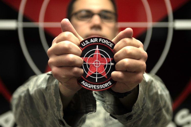 U.S. Air Force Staff Sgt. William Heines, 18th Aggressor Squadron baron controller, holds the unit patch which is adorned with its symbolic red star May 12, 2015, at Eielson Air Force Base, Alaska. The patch's star and yellow hammer-and-sickle symbolizes the Soviet Union, the United States' enemy during the Cold War. (U.S. Air Force photo by Staff Sgt. Shawn Nickel/Released)