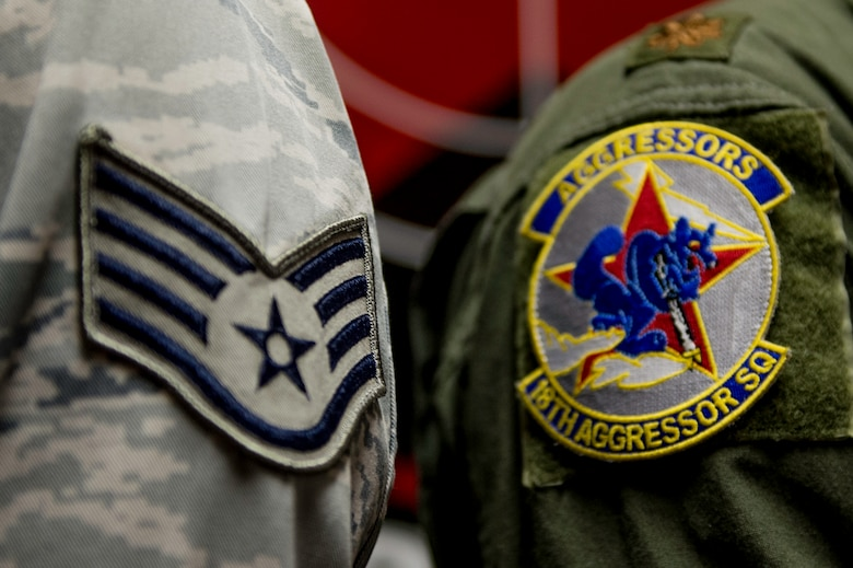 U.S. Air Force Staff Sgt. William Heines, an 18th Aggressor Squadron baron controller, shows his enlisted stripes in relation to a pilot's squadron patch May 12, 2015, at Eielson Air Force Base, Alaska. Both Aggressor pilots and barons spend a large amount of time studying enemy aerial battle tactics from around the world and teach others how combat these threats. (U.S. Air Force photo by Staff Sgt. Shawn Nickel/Released)