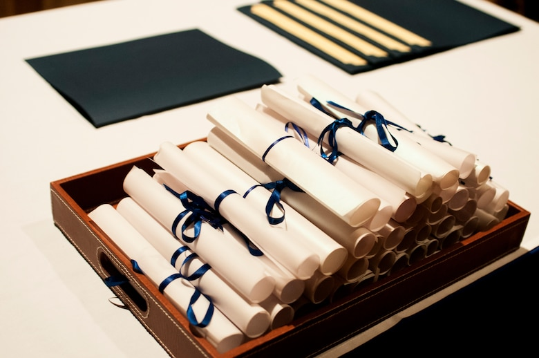 Diploma certificates sit on a table during the Community College of the Air Force graduation ceremony at the base theater on Goodfellow Air Force Base, Texas, May 8, 2015. The ceremony also included the Pitsenbarger awards and Powell Warrior award. (U.S. Air Force photo by Senior Airman Scott Jackson)
