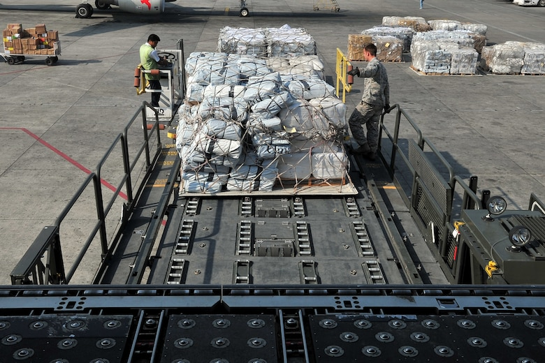 Staff Sgt. Josh Foley, a 36th Mobility Response Squadron aerial port supervisor, and a Nepalese official help unload relief supplies from an MD-11 cargo aircraft at the Tribhuvan International Airport in Kathmandu, Nepal, May 11, 2015. The Nepalese army and Airmen worked together to process 509,380 pounds of cargo in a 24-hour period from nine aircraft delivering relief supplies after a 7.8-magnitude earthquake struck the nation April 25. (U.S. Air Force photo/Staff Sgt. Melissa B. White)