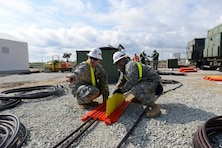 Sgt. Zackery Slater, left, from Warrenton, Va., and Sgt. Win Htun, from New York, route power cables at Naval Support Facility Deveselu, Romania, April 19, 2015. The Soldiers are assigned to 249th Engineer Battalion from Fort Belvoir, Va., and helped...