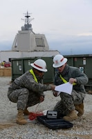 Sgt. Win Htun, left, and Sgt. Corey Good look over instructions before testing for electrical ground at Naval Support Facility Deveselu, Romania, April 19, 2015. Htun, from New York, and Good, from Moline, Ill., are assigned to the 249th Engineer...