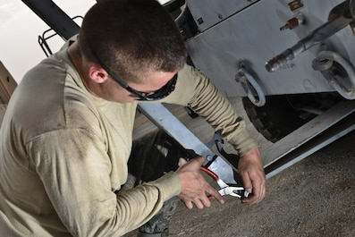 Senior Airman Daniel Suarez, 379th Expeditionary Maintenance Squadron, fastens a linchpin on a tow bar for an aircraft air conditioning unit May 7, 2015 at Al Udeid Air Base, Qatar. Even through wet-bulb globe temperature index of black flag conditions, airmen remain resilient and practice safe measures to ensure their wingman and themselves are protected from the extreme sun and heat wearing eye protection and sometimes long sleeves. (U.S. Air Force photo by Staff Sgt. Alexandre Montes)
