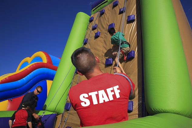 Combat Center children scale an inflatable rock climbing wall during the Family Fun Day event as part of the 'We Salute You Fest' at Lance Cpl. Torrey L. Gray Field, May 9, 2015. Other activities available during the Family Fun Day event included; balloon artists, a henna tattoo station, a face painting station, a Ferris wheel and static displays of military vehicles.(Official Marine Corps photo by Pfc. Levi Schultz/Released)