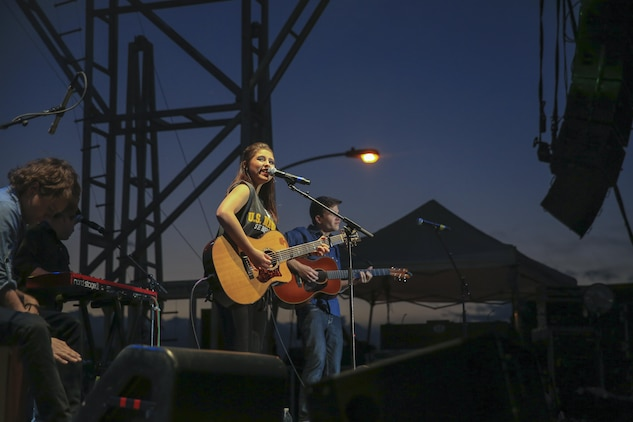 Caroline Kole, country music singer, performs for Marines, sailors and their families during the 'We Salute You Fest' at Lance Cpl. Torrey L. Gray Field, May 9, 2015. The event was free to all hands aboard the Combat Center. (Official Marine Corps photo by Pfc. Levi Schultz/Released)