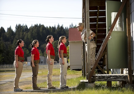 JOINT BASE LEWIS-MCCHORD, Wa. -- Gunnery Sgt. Agustin Juradosegovia, a sergeant instructor from Oxnard, California, instructs Marine Corps officer candidates before they enter barracks during Officer Candidates School preparation at Joint Base Lewis-McChord, Washington, May 8, 2015. During the three-day event, Seattle-based sergeant instructors and officer recruiters worked together to physically and mentally prepare candidates for the rigors of OCS, which the candidates will later attend aboard Marine Corps Base Quantico, Virginia. The candidates pictured are (left to right) Nicole Compton from Seabeck, Washington; Anna Sigel from Lancaster, Pennsylvania; Tess Carlin from Auburn, Washington; and Sydney Williams from Bremerton, Washington. (U.S. Marine Corps photo by Sgt. Reece Lodder)