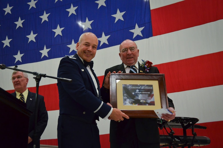 Col. Daniel Yenchesky, the 128th Air Refueling Wing commander, presents the Honored Citizen Award to Joseph Kotarak, Jr. at the 35th annual Civic Dinner Dance in the aircraft hangar here May 14, 2015.  The Civic Dinner Dance is an event coordinated by the Milwaukee Armed Forces Committee for Wisconsin military members, elected state and local officials, and citizens of the local Milwaukee area to celebrate community relations during Armed Forces Week.  (U.S. Air National Guard photo by Tech. Sgt. Jenna Lenski/Released)