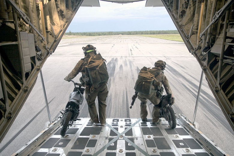 Two 123rd STS personnel off load 50 cc mini bikes to stage on a runway at an Eglin Air Force Base drop zone, prior to a static line jump and jump clearing team mission from a KC-130J Super Hercules belonging to Marine Aerial Refueler Transport Squadron 252, during Emerald Warrior 2015, April 28, 2015. The mini bikes are used to patrol down the air strip before the plane lands to ensure there is no debris or hostile forces near the landing zone. Emerald Warrior is a joint exercise led by Air Force Special Operations Command that provides pre-deployment training for U.S. and partner nation special operations forces and interagency elements.