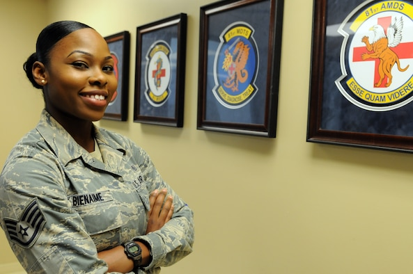 Staff Sgt. Jasmine Bienaime, an 81st Surgical Operations Squadron women's health medical technician, poses for a photo in front of Keesler Medical Center's squadron crests May 12, 2015, Keesler Air Force Base, Miss. Bienaime has been a member of the Air Force for almost five years and sewed on staff sergeant in April of this year. (U.S. Air Force photo by Airman 1st Class Duncan McElroy)