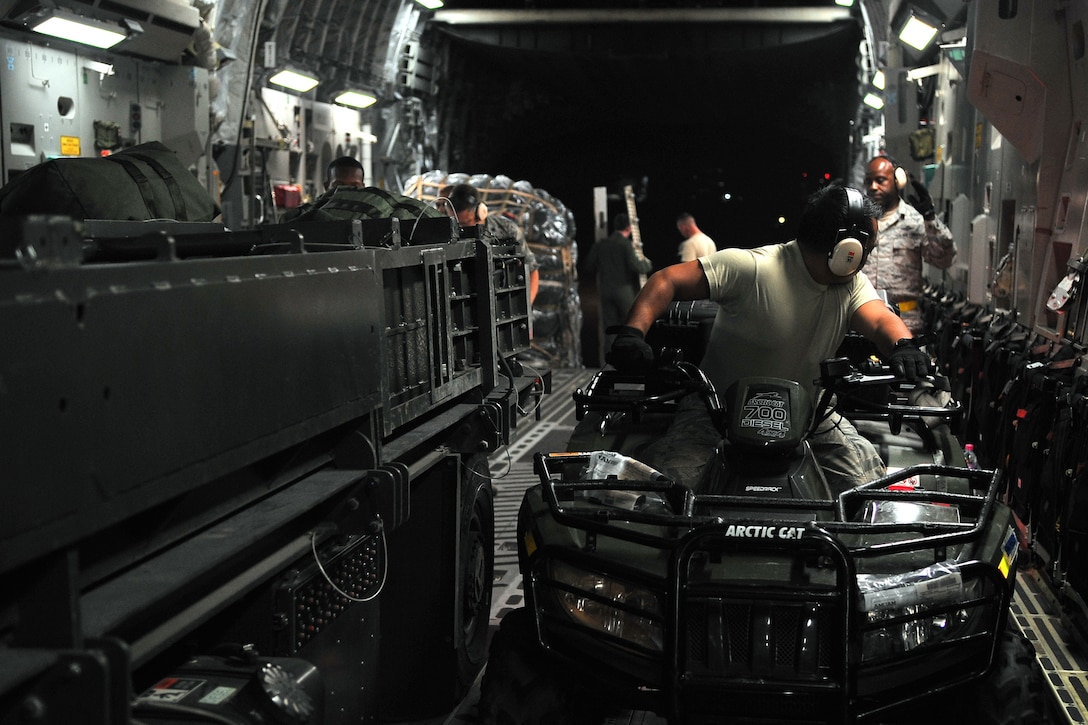 Senior Airman Louie Lacsina, a 36th Mobility Response Squadron air transportation specialist, unloads vehicles from a C-17 Globemaster III at Tribhuvan International Airport, Nepal, May 5, 2015. The 36th CRG is a rapid-deployment unit designed to establish and maintain airfield operations in a forward operating location. The unit joined the U.S. Department of State- and U.S. Agency for International Development-led humanitarian assistance and disaster relief operations in support of the government and armed forces of Nepal. (U.S. Air Force photo/Staff Sgt. Melissa White)