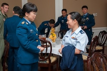 Capt. Shaoping Mo, right, a participant of the Language Enabled Airman Program, right, speaks with a member of the visiting Chinese delegation.  Maj. Gen. Han Xing, deputy commandant of the People's Liberation Army Air Force Command College, along with PLAAF Command College instructors and students, visited Air University headquarters and various AU schools, April 29, 2015. (U.S. Air Force photo by Melanie Rodgers Cox)