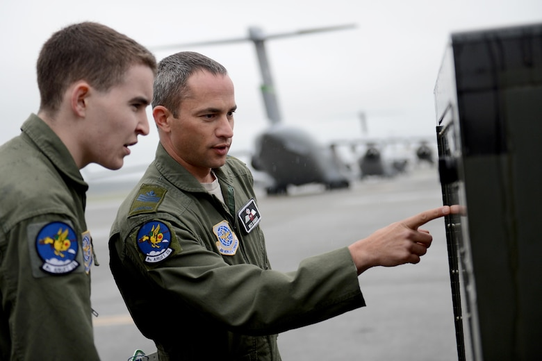 Royal Canadian Air Force Sgt. Wes Ramsay (right), and U.S. Air Force Airman 1st Class Travis Hoose, both 8th Airlift Squadron loadmasters, inspect a generator May 12, 2015, at Joint Base Lewis-McChord, Wash. Ramsay is a part of the military exchange program and works as a loadmaster instructor with the 8th AS. (U.S. Air Force photo/Airman 1st Class Keoni Chavarria)