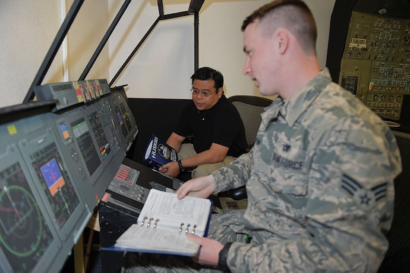 Jolly Tangog, an equipment specialist with Air Force engineering and technical services for the 732nd Air Mobility Squadron, supervises Senior Airman Adam Orton, a jets lead technician, as he uses a C-5M Super Galaxy maintenance trainer on Joint Base Elmendorf-Richardson, Alaska, May 7, 2015. Tangog came up with the cost-saving idea to build a trainer at Elmendorf rather than sending Airmen away on a temporary duty for expensive refresher training. (U.S. Air Force photo/Alejandro Pena)