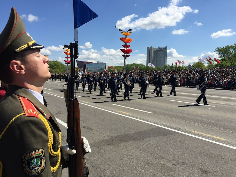 An Armed Forces of the Republic of Belarus soldier provides an honor guard as 34 Airmen from the U.S. Air Forces in Europe Band march in the World War II Victory Day Parade May 9, 2015, in Minsk, Belarus. The band's involvement is the first time in Belarus' history that participants from the U.S. Defense Department marched in the parade. The event commemorated the sacrifices of the World War II Allies and the end of hostilities 70 years ago. In addition to their participation in the Victory Day parade, which included more than 5,000 Belarusian soldiers and 250 military vehicles, the USAFE bandsmen performed in concerts in Brest and Minsk, Belarus. (U.S. Air Force photo/Master Sgt. Brian Bahret)
