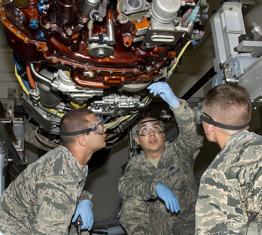 U.S. Air Force Staff Sgt. Edgar Cadenas, 362nd Training Squadron crew chief instructor, demonstrates how to replace an engine fuel filter on a F119-PW-100 engine for the F-22 steps to Airman Dylan Tyrrell and Airman Matei Craven, students from 362nd Training Squadron at Sheppard Air Force Base, Texas, May 13, 2015. Students learn how to perform inspections to ensure there are no deficiencies that may hinder an aircraft's flying capabilities. (U.S. Air Force photo by Danny Webb)