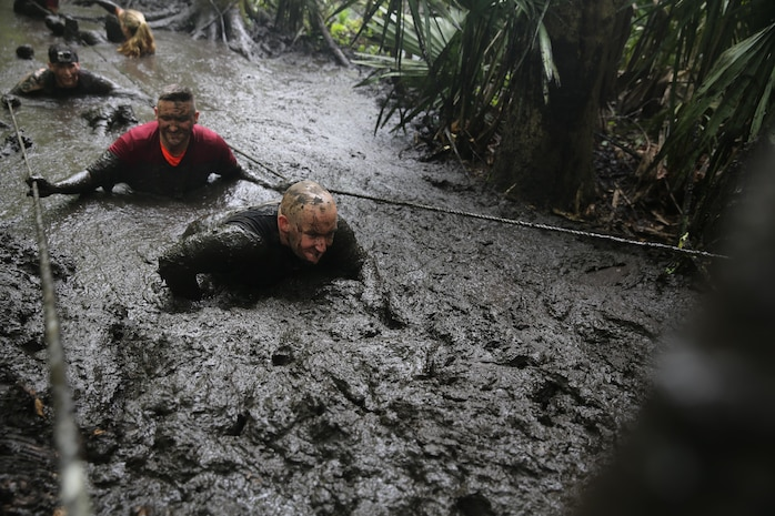 Participants of the MARSOC Mud, Sweat and Tears run wade through one of the larger mud-filled trenches featured in the mud run course aboard Stone Bay, on Marine Corps Base Camp Lejeune, N.C., April 25, 2015. (U.S. Marine Corps photo by Cpl. Steven Fox/Released)