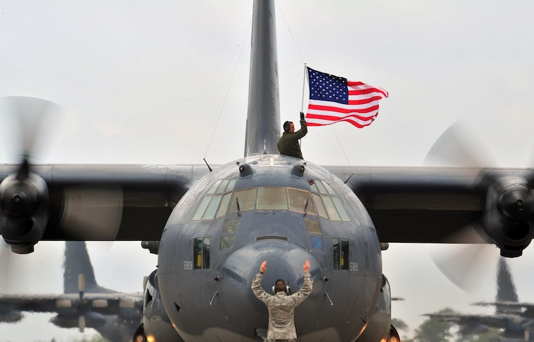 An aircrew member flies an American flag out of the top of an MC-130P Combat Shadow, May 15, 2015, at Hurlburt Field, Fla. The final two MC-130P Combat Shadow aircraft in the Air Force landed for the last time at Hurlburt Field, Fla., in front of more than 400 people and will take their last flight to the boneyard at Davis-Monthan Air Force Base, Arizona, June 1. (U.S. Air Force photo/Airman 1st Class Ryan Conroy)