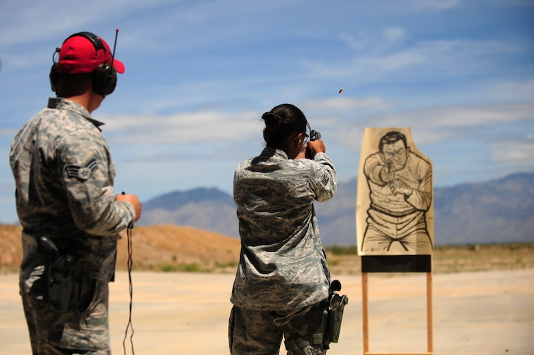 U.S. Air Force Staff Sgt.  Maeve Kaneakalau, 355th Security Forces member, fires her weapon at a target as Senior Airman Ethan Talbot, 355th SFS combat arms instructor, observes during the practice round of a firing competition in honor of National Police Week at Davis-Monthan Air Force Base, Ariz., May 13, 2015. National Police Week pays special recognition to law enforcement officers who have lost their lives in the line of duty. (U.S. Air Force photo by Airman 1st Class Chris Drzazgowski/Released)