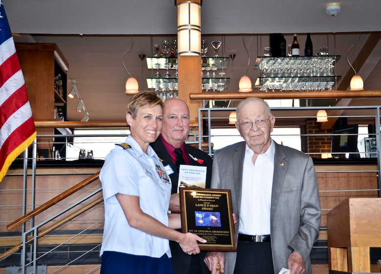 Capt. Amy Concanour and retired Capt. Tom Plantenberg, present the Lance Sijan Award to Ceylon Gruenstern at the Milwaukee Yacht Club May 15, 2015 for his service during World War II. Gruenstern is the great-grandfather of Senior Airman Melissa Mussa, 128th Air Refueling Wing civil engineering squadron.  (U.S. Air National Guard photo by Capt. Matthew Wunderlin/Released)