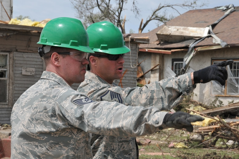 DELMONT, S.D. - Master Sgt. Jacob Erpenbach, 114th Civil Engineer Squadron engineer assistant, directs Tech. Sgt. Zach Jorgenson, 114th Civil Engineer Squadron HVAC superintendent, on the location of the next area to be cleared during the unit's state activation in support of the community of Delmont, S.D.  The unit was sent to Delmont to assist with the tornado recovery efforts after the city was hit by a tornado May 11, 2015.(National Guard photo by Senior Master Sgt. Nancy Ausland/released)