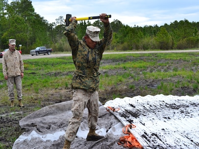 PFC Rai drives an anchor into the ground to secure the matting.