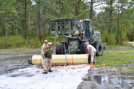 The Marines of the Maintenance platoon not only provided heavy equipment (HE), the heavy equipment operators (Military Occupational Specialty (MOS) 1345) to load and unload the rolls of matting, the Medium Tactical Vehicle Replacements (MTVRs) and drivers (MOS 3531) to test the trafficability of the systems on the different terrains; they served as the labor force to employ the matting.  LCpl Bailey operates the TRAM while Cpl Regier stabilizes the matting on the ground.