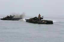 """An Amphibious Assault Vehicle with AAV Platoon, Company B, Ground Combat Element Integrated Task Force, maneuvers around a """"disabled"""" AAV in the Pacific Ocean during a Marine Corps Operational Test and Evaluation Activity assessment May 11, 2015, near Red Beach training area, aboard Marine Corps Base Camp Pendleton, California. The GCEITF AAV Platoon is executing the final phase of their Marine Corps Operational Test and Evaluation Activity assessment by conducting beach and water-borne tasks. From October 2014 to July 2015, the GCEITF will conduct individual and collective level skills training in designated ground combat arms occupational specialties in order to facilitate the standards-based assessment of the physical performance of Marines in a simulated operating environment performing specific ground combat arms tasks. (U.S. Marine Corps photo By Gunnery Sgt. Matt Epright/Released)"""